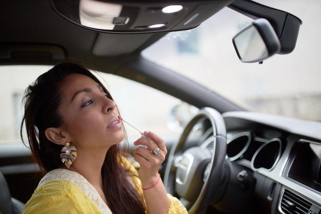 Mujer latina en vestido amarillo pintando sus labios dentro de un coche.