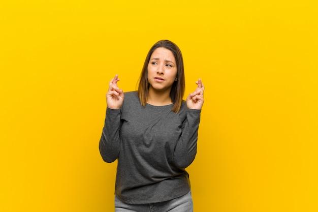 Mujer latinoamericana cruzando los dedos con ansiedad y esperando buena suerte con una mirada preocupada aislada en la pared amarilla