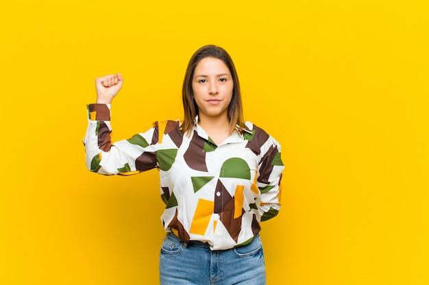 Mujer latinoamericana sintiéndose seria, fuerte y rebelde, levantando el puño, protestando o luchando por la revolución aislada contra la pared amarilla