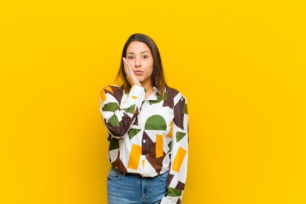 Mujer latinoamericana sintiéndose sorprendida y asombrada sosteniendo cara a mano con incredulidad con la boca abierta sobre la pared amarilla