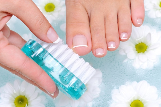 Mujer lava y limpia las uñas de los pies a pie en agua.