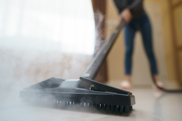 Mujer lava el piso con un trapeador a vapor.