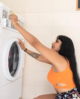 Mujer lava su ropa en una lavandería de monedas