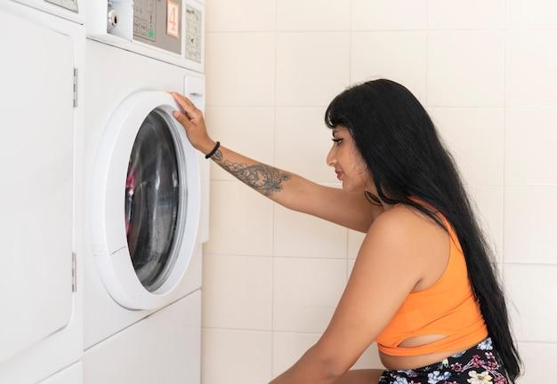 Mujer lava su ropa en una lavandería