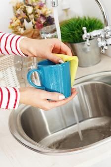 Mujer lava la taza de té