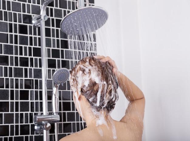Mujer lavando la cabeza y el cabello en la ducha de lluvia con champú, vista posterior