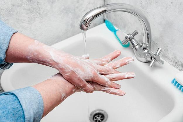 Mujer lavando muy cuidadosamente las manos con jabón durante el coronavirus epidémico.