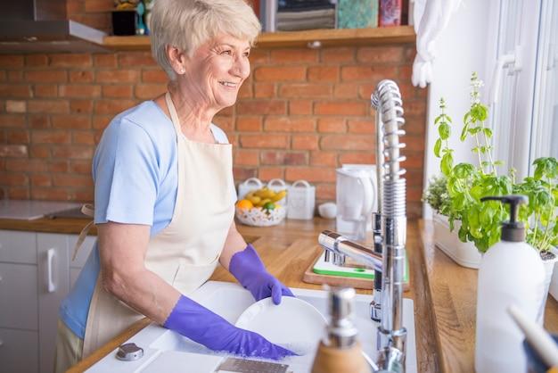 Mujer lavando platos delante de la ventana