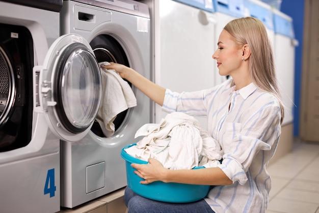 Mujer lavando ropa - sacando prendas blancas de la lavadora, poniéndola en la canasta, lavabo. en la casa de lavado