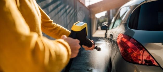 Mujer lavando su coche con agua a presión
