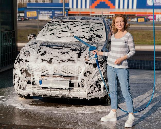 Mujer lavando su coche al aire libre
