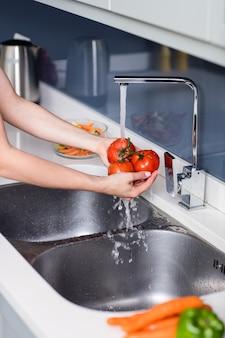 Mujer lavando tomates en el fregadero de la cocina