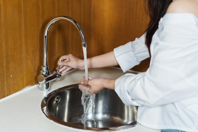 Mujer lavándose las manos en la cocina