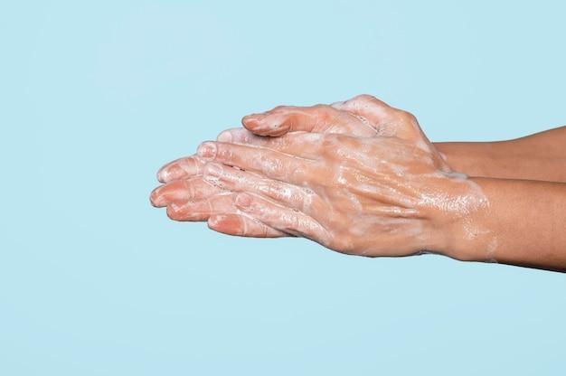 Mujer lavándose las manos aisladas en azul