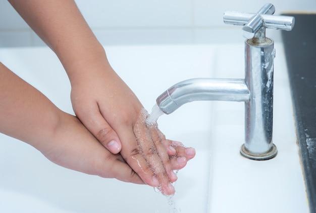 Mujer lavándose las manos debajo del grifo con agua pura y clara