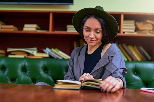 Mujer de lectura de moda con estilo descansando sola y disfrutando del libro de novela romántica en la tienda de la biblioteca