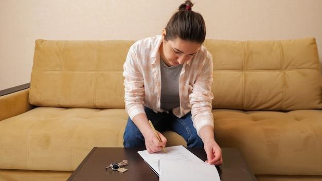 Mujer lee contrato de compra de apartamento en la mesa en la habitación