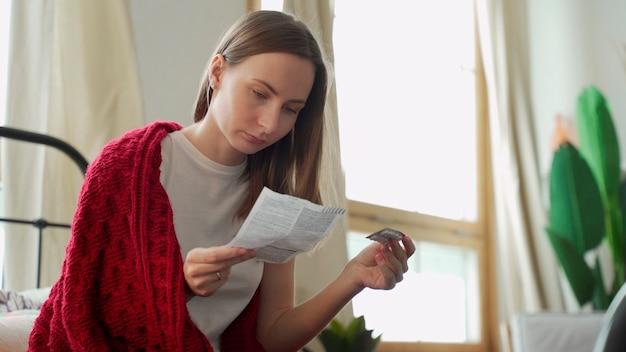 La mujer lee las instrucciones de la píldora, sentada en la cama cubierta con una manta