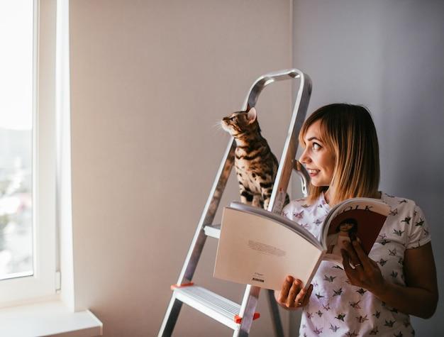 La mujer lee un libro mientras que el gato de bengala se coloca en la escalera detrás de ella