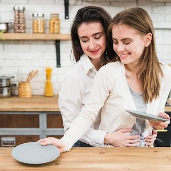 Mujer lesbiana sonriente que sirve platos en la mesa de madera en la cocina