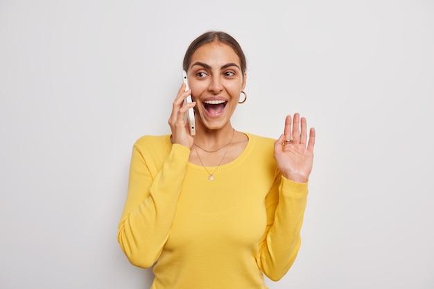 La mujer levanta la palma de la mano a través de un teléfono inteligente hace una llamada y sonríe felizmente vestida con un puente amarillo informal plantea sobre blanco