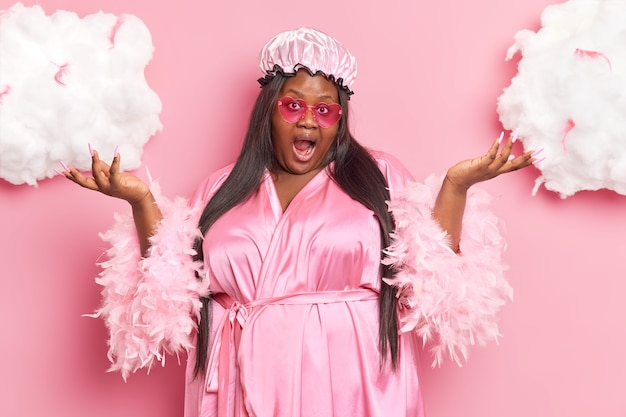 La mujer levanta las palmas con incertidumbre exclama en voz alta confundida por una situación inesperada viste ropa doméstica plantea en rosa