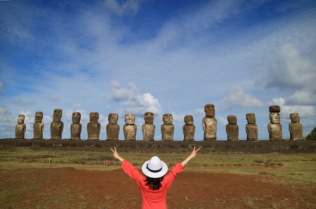 Mujer levantando los brazos felizmente delante de las estatuas moai de ahu tongariki, isla de pascua, chile