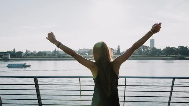 Mujer levantando los brazos frente al río al aire libre