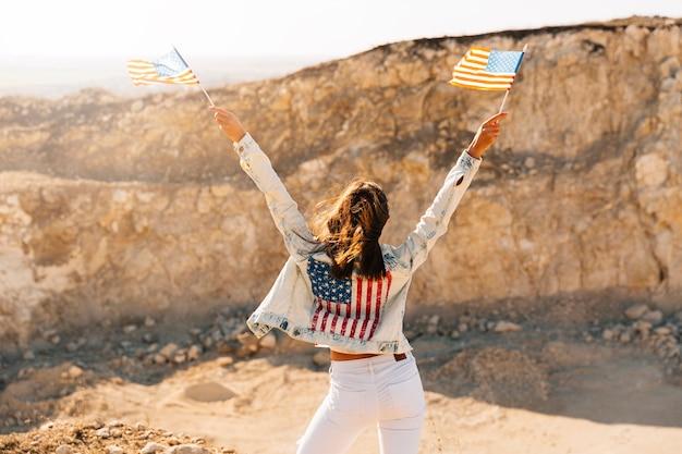 Mujer levantando manos con banderas en la montaña