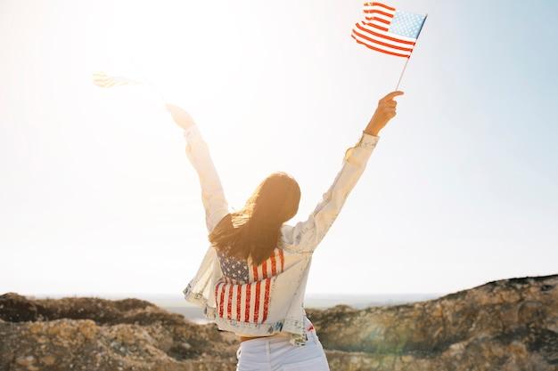 Mujer levantando las manos con banderas en la montaña