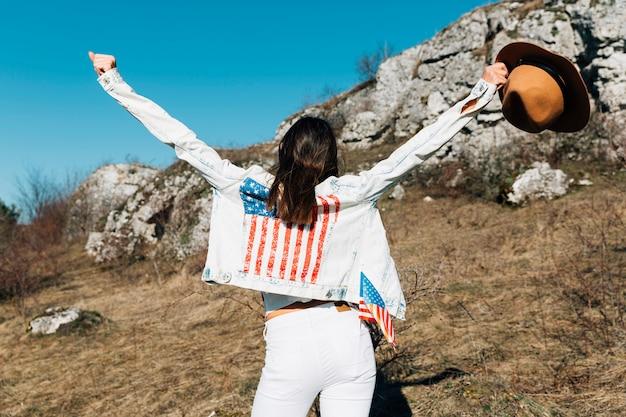 Mujer levantando las manos con sombrero en la naturaleza