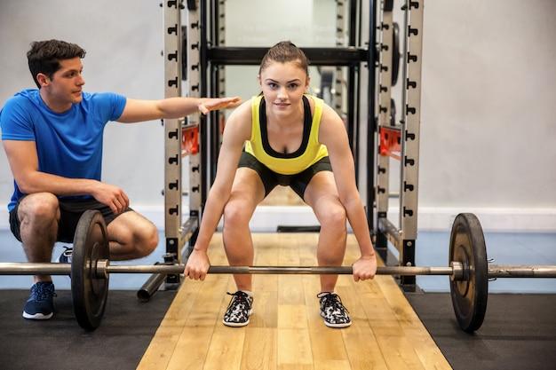 Mujer levantando pesas y pesas con entrenador viendo