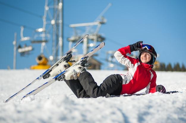 Mujer levantando sus gafas de esquí y mirando a otro lado, acostada con esquís en la nieve en la cima de la montaña en un día soleado