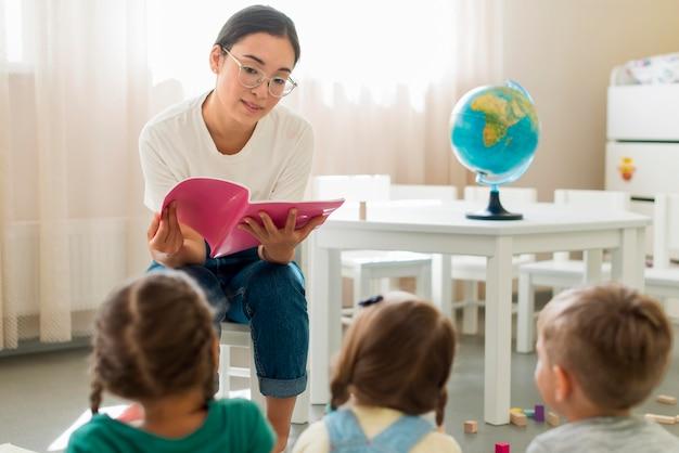 Mujer leyendo algo para sus alumnos