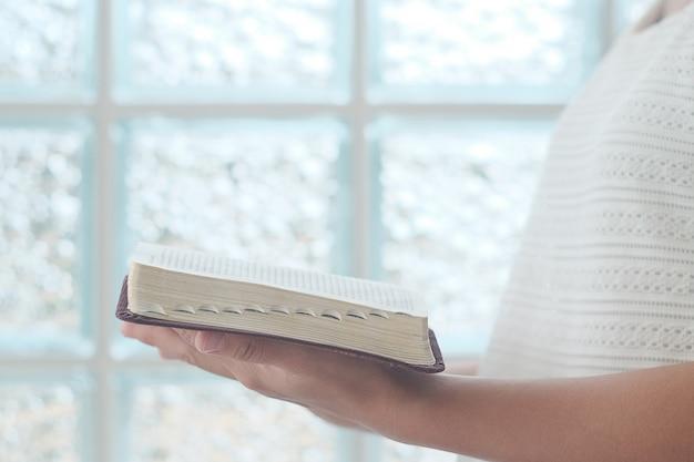La mujer está leyendo la biblia.