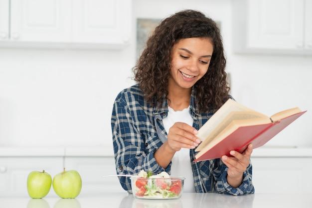 Mujer leyendo junto a manzanas verdes