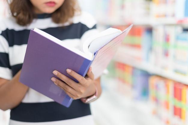 Mujer leyendo un libro en la biblioteca, enfoque selectivo