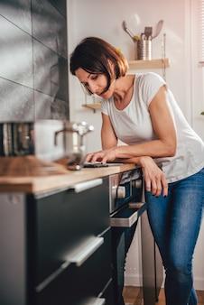 Mujer leyendo el libro de cocina en línea