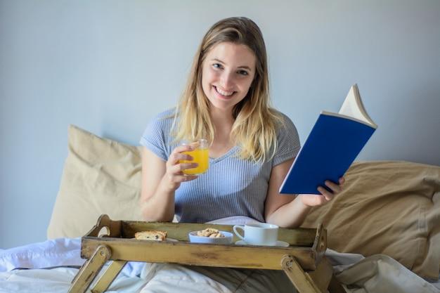 Mujer leyendo un libro y desayunando.