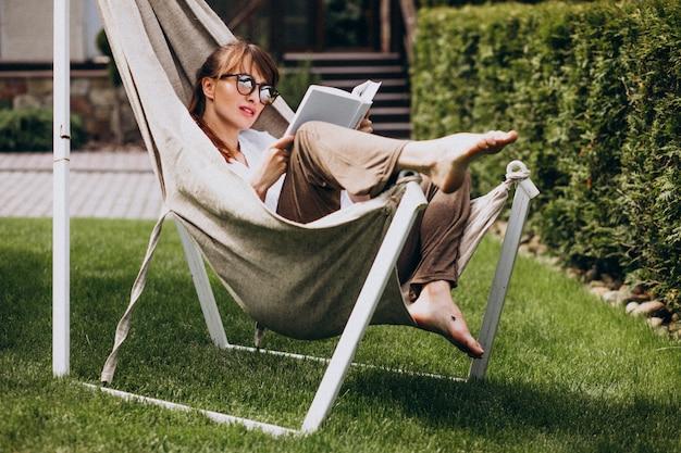 Mujer leyendo un libro en el jardín junto a la casa