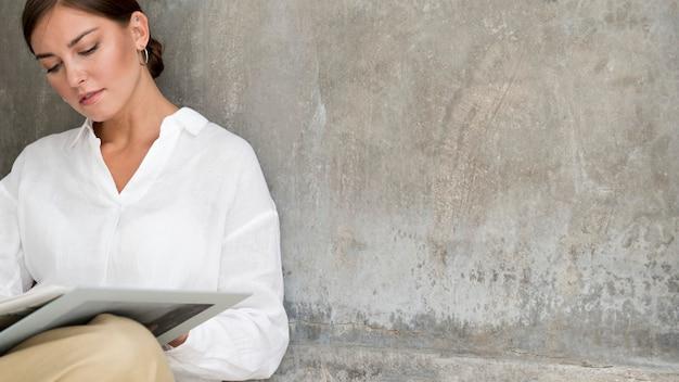 Mujer leyendo un libro junto a una pared de cemento