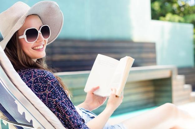 Mujer leyendo un libro junto a la piscina