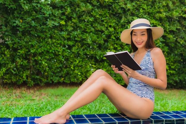 Mujer leyendo libro junto a la piscina