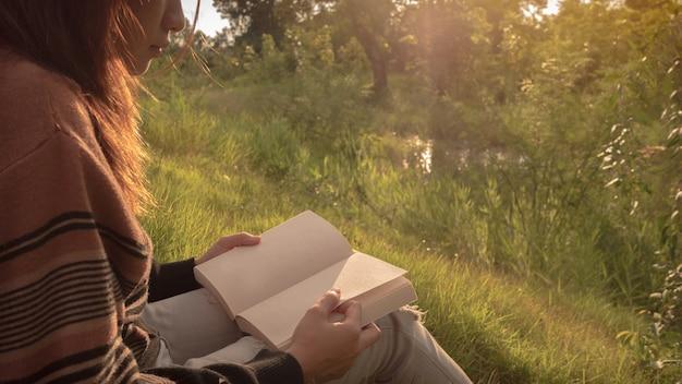 La mujer leyendo el libro en la naturaleza.