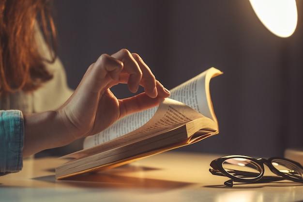 Mujer leyendo un libro en la noche en casa cerca
