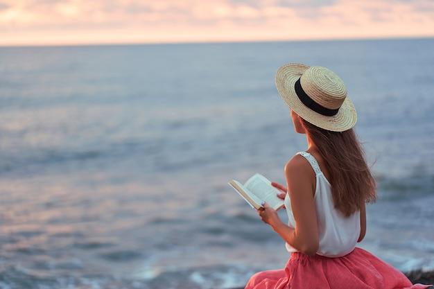 Mujer leyendo un libro de novelas en la orilla del mar