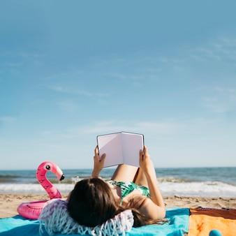Mujer leyendo libro en la playa