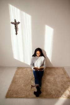 Mujer leyendo un libro sagrado en el interior