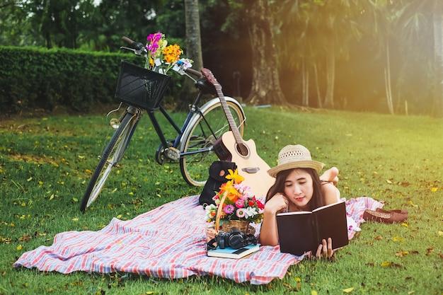 Mujer leyendo un libro sobre la relajación del tiempo. señora asiática tiene comida campestre