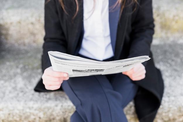 Mujer leyendo periódico afuera